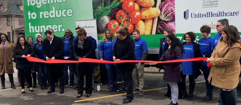 Red ribbon cutting formal unveiling of a new food bank distribution truck.